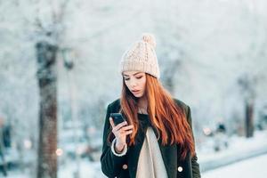 ung kvinna i vinterparken pratar mobiltelefon, sms foto