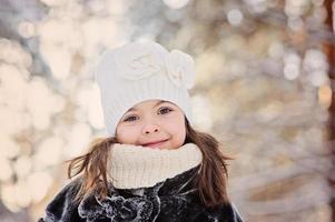 glad barnflicka på promenad i snöig vinterskog foto