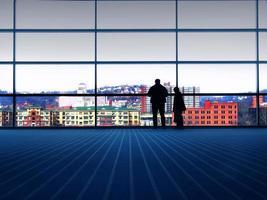 ett stort fönster där två personer tittar ut mot staden foto