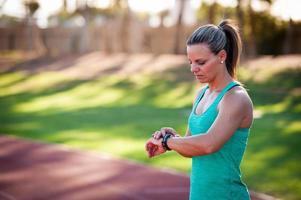 bild av en kvinnlig idrottsman som justerar sin pulsmätare foto