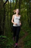 vacker ung kvinna kör i skogen - aktiv löpare spring foto