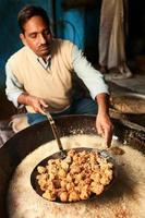 indisk gatuförsäljare som förbereder mat foto
