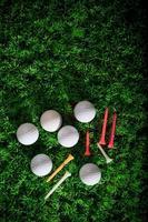golfboll och tee på grönt gräs foto