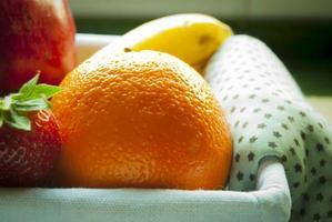 färsk frukt i rottingkorg med trasa foto