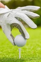 kvinnans hand sätter snyggt bollen på tee på fältet