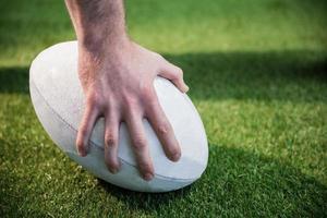 rugbyspelare som poserar en rugbyboll foto