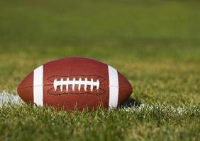 amerikansk fotboll på fält med gårdslinje och gräs foto