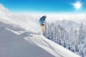man skidåkare springer nedförsbacke foto