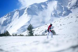 snowboardåkare som klättrar uppför sluttningen foto
