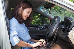 asiatisk kvinna med en bärbar dator i sin bil foto