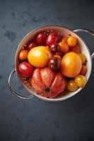 blandade tomatsorter i ett durkslag foto