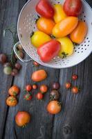 tomater på det gamla träbordet. färgglada tomater foto