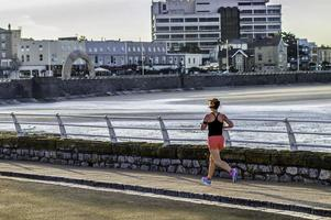 kvinna, jogging, morgonkörning vid havet, färgbild. foto