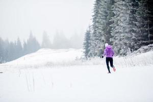 löpande kvinna, vinterjogginspiration och motivation foto