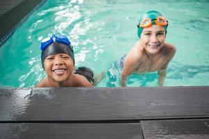 små pojkar som ler i poolen foto