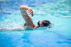 ung man simmar i en pool foto
