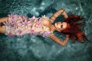 porträtt av vacker rödhårig tjej i vattnet foto