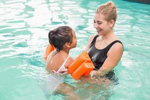 söt liten flicka som lär sig att simma med tränaren