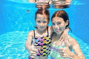 glada aktiva barn leker under vattnet i poolen foto