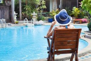 kvinna avkopplande nära poolen foto