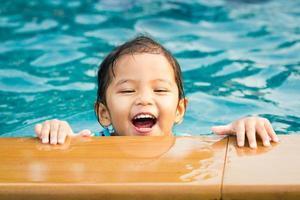 en liten flicka som simmar i en pool foto