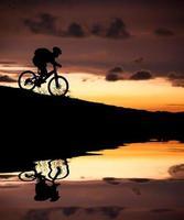 silhuett av mountainbiker med reflektion och solnedgång