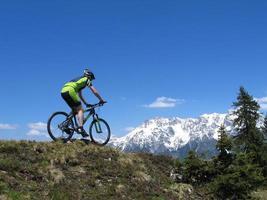mountainbiker ridning genom bergen foto