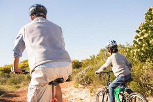 far och son på cykeltur foto