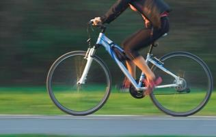 kvinna cyklar - suddig rörelse foto