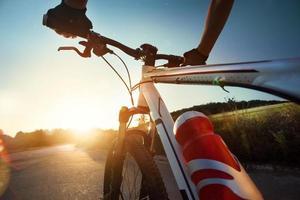 händer i handskar som håller styret på en cykel foto