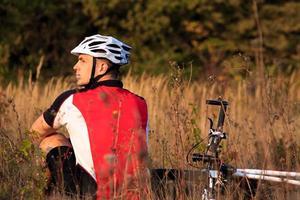 mountainbike cyklist som vilar utomhus med sin cykel foto