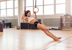 ung fit kvinna som gör pull-ups på gymnastiska ringar foto