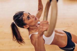 ung fit kvinna som drar upp gymnastiska ringar foto