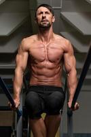 passande idrottsman som gör träning på parallella barer foto