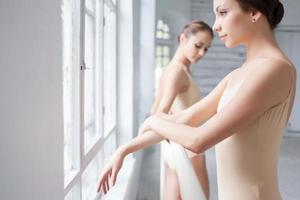 de två klassiska balettdansarna som poserar på barre