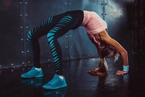 bridge utgör sportig kvinna gör gymnastik yoga stretching gymnastik foto