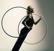 gymnast i svart hudtät klänning med två gymnastiska ringar foto