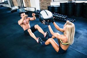 muskulös man och kvinna träning med fitball foto