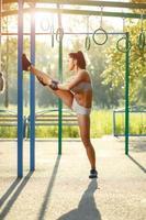 vacker kvinna som gör sportsträckningsövningar på sommaren utomhus. foto