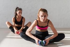 två passande tjejer som gör stretchövning tillsammans sitter på foto