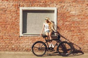vacker ung kvinna med cykel utomhus foto
