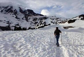 ung man vandrar i snö på mt. ranier nationalpark foto
