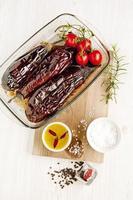 rostad aubergine & körsbärstomater i ugnsbricka på vitt. säsong foto