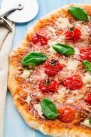pizza med körsbärstomater och basilika foto