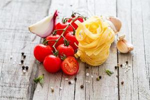 rå pasta, tomat, basilika foto