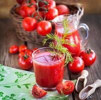 tomatsaft och färska tomater foto