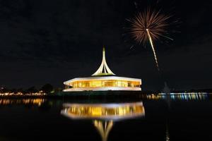 monument vid den offentliga parken mot vatten med nattljus.