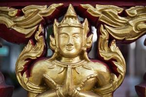 buddhistisk ängel snidad figur i sawasdee-action foto