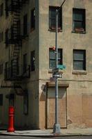 en ljusröd brandpost bredvid en byggnad foto