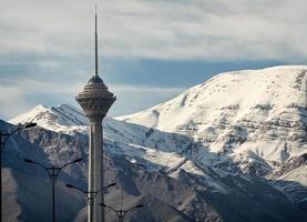 milad tornet i Teheran framför snö täckta alborz bergen foto